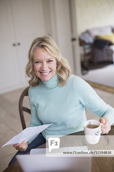 Portrait smiling  confident female freelancer working at laptop and drinking tea at home
