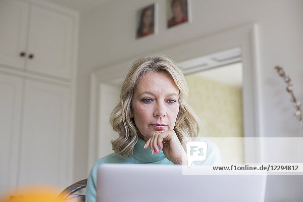 Focused mature female freelancer working at laptop at home