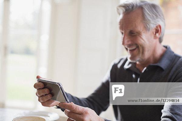 Smiling mature man using smart phone