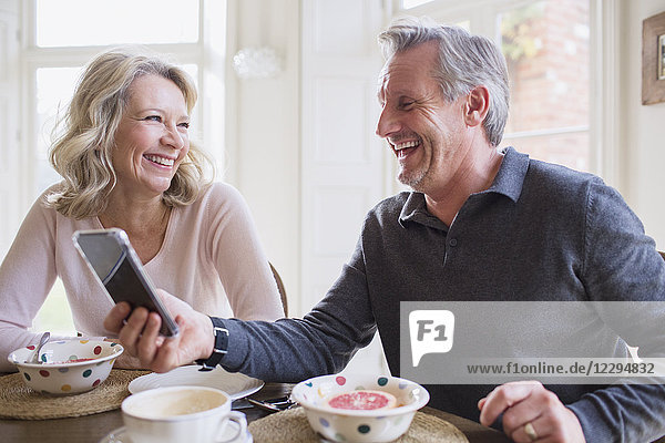 Laughing mature couple using smart phone and eating breakfast