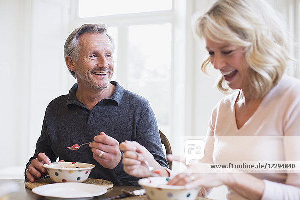 Smiling mature couple eating breakfast