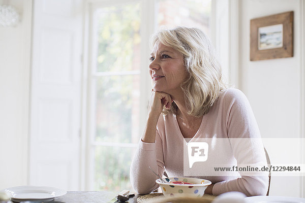 Smiling  satisfied mature woman eating breakfast