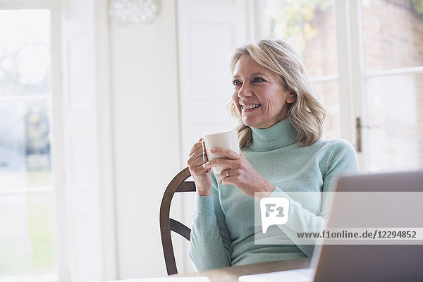 Smiling mature female freelancer drinking tea and working at laptop at home