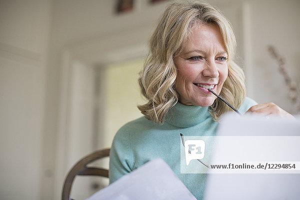 Smiling mature female freelancer working at laptop at home