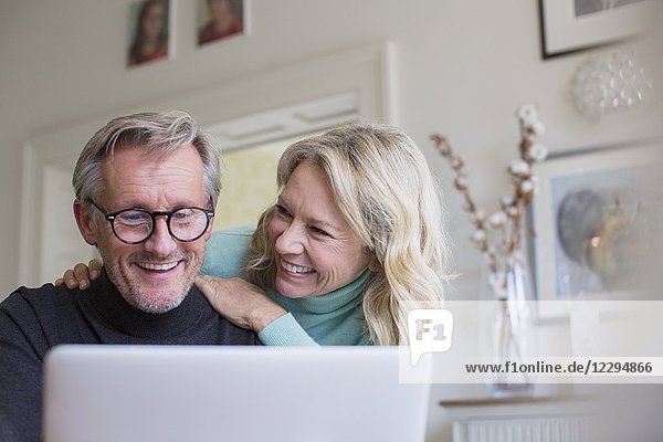 Smiling mature couple using laptop