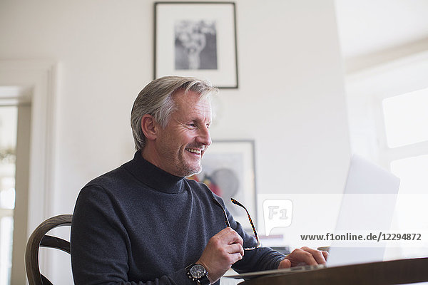 Smiling mature male freelancer working at laptop at home