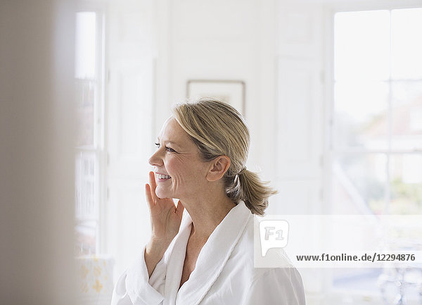 Smiling mature woman applying moisturizer to face in bathroom