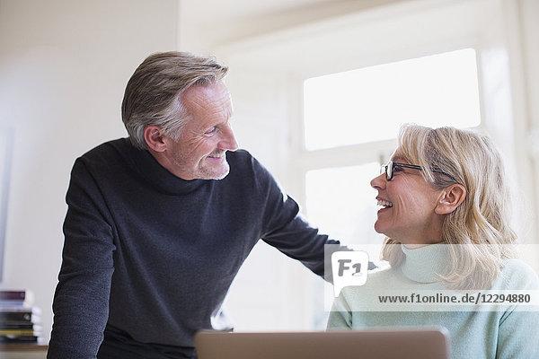 Smiling mature couple talking at laptop