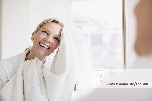 Smiling mature woman drying face with towel at bathroom mirror