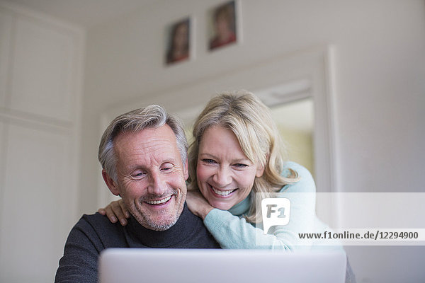Smiling  happy mature couple using laptop
