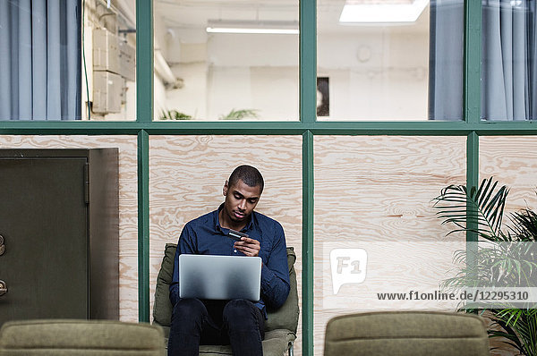 Businessman shopping online with credit card through laptop while sitting at creative office