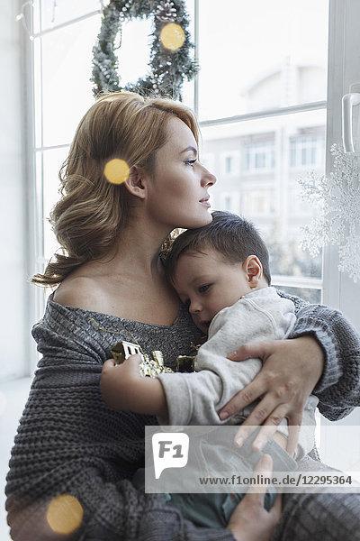Junge Frau sitzend mit Sohn am Fenster zu Hause