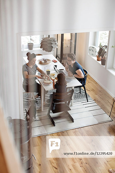 High angle view of mothers talking to daughter having breakfast at dining table