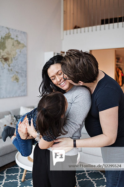Woman kissing girlfriend with daughter in living room at home