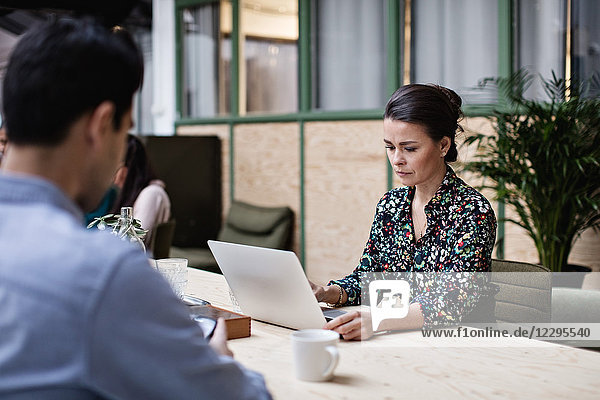Businesswoman using laptop while sitting with colleague at table in office