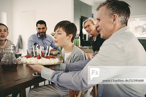 Boy blowing candles on birthday cake while sitting with family during party