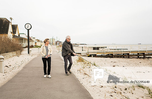 Senior couple walking with Schnauzer on footpath at beach against clear sky