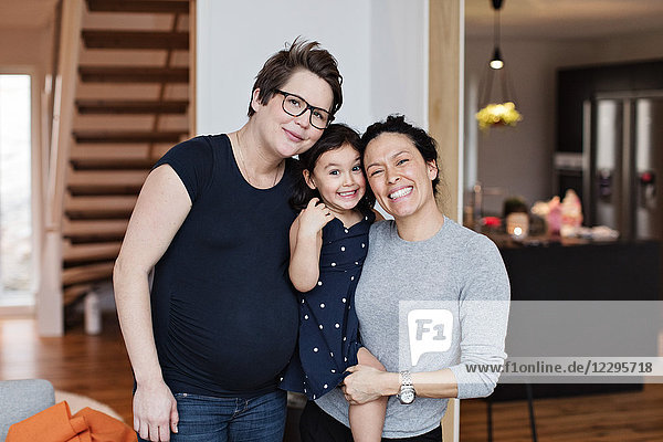 Portrait of smiling lesbian couple with daughter in living room at home