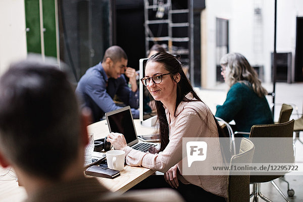 Male and female business colleagues discussing in meeting at table in creative office