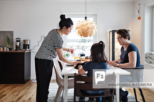Female serving food to girl and woman at dining table