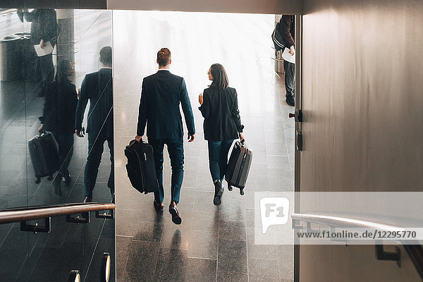 Full length rear view of business people walking in airport