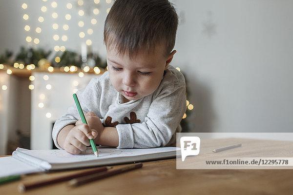Süßer Junge beim Zeichnen auf Buch am Tisch