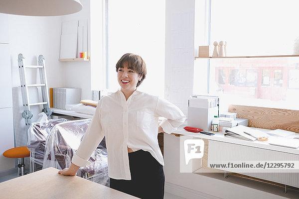 Smiling female design professional standing at desk in workshop