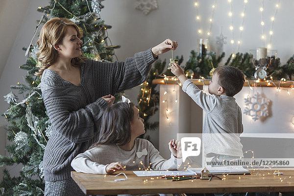 Verspielte Frau mit Kindern zu Hause zu Weihnachten