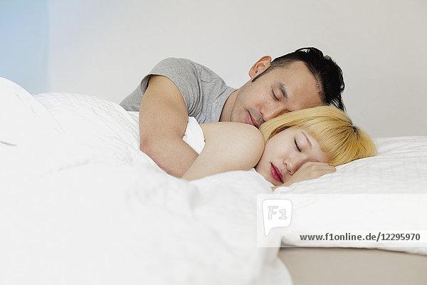 Junges Paar schläft zu Hause auf dem Bett gegen die Wand