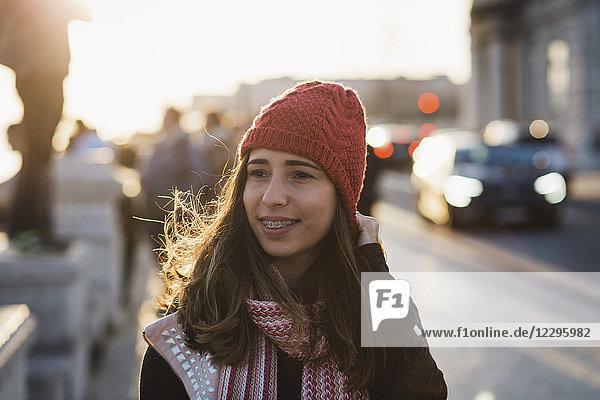 Lächelnde erwachsene Frau mit Strickmütze  die bei Sonnenuntergang in der Stadt unterwegs ist.