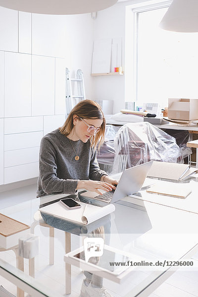 Young female owner using laptop at desk in workshop