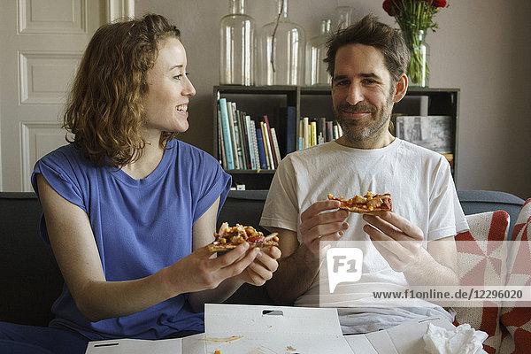 Fröhliches  erwachsenes Paar auf dem Sofa sitzend  frische Pizza im Wohnzimmer zu Hause essend.