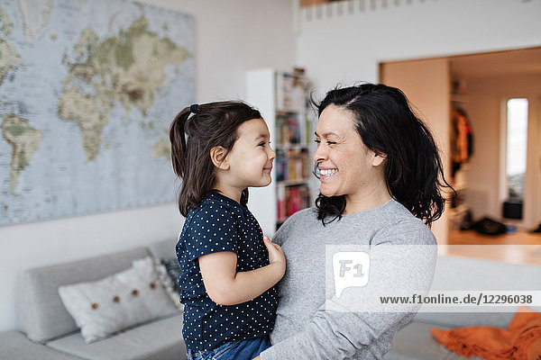 Smiling mother carrying daughter while standing at home