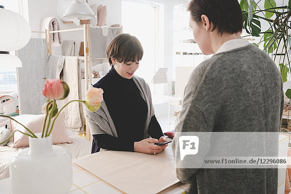 Female customer using smart phone in front of owner at upholstery store