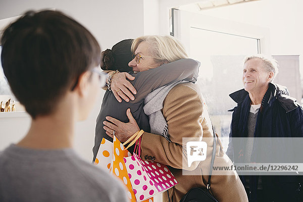 Senior woman embracing daughter while standing at doorway with family