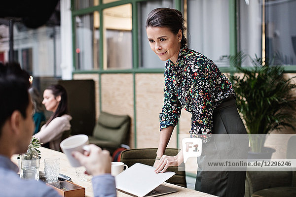Businesswoman holding laptop while looking at coworker in office
