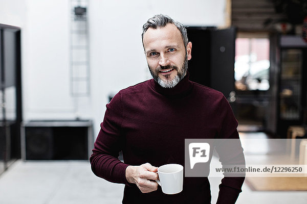 Portrait of smiling mature businessman having coffee while standing at creative office