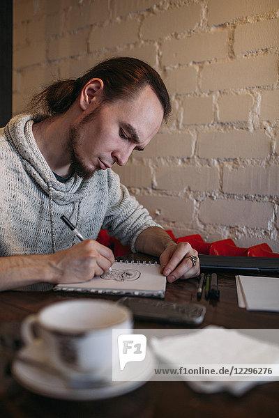 Junger Mann malt Buch auf Tisch im Cafe