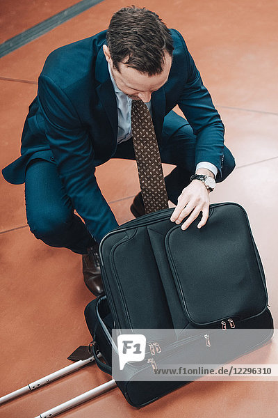 High angle view of businessman with suitcase at subway station