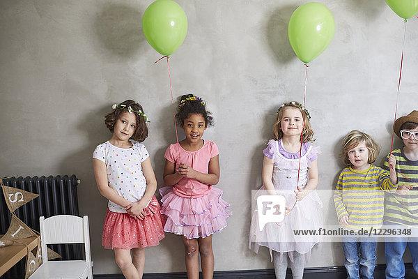 Porträt von Mädchen und Jungen mit grünen Luftballons  die an der Wand stehen