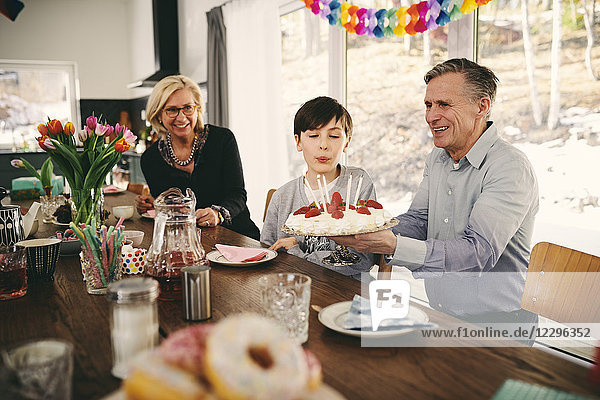 Boy blowing candles on birthday cake while sitting with grandparents at table