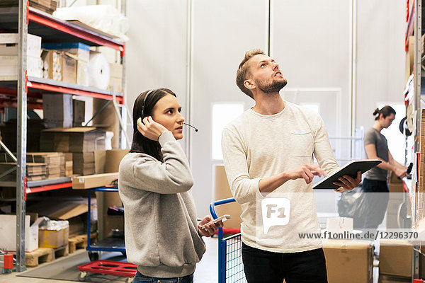 Man and woman examining boxes at distribution warehouse