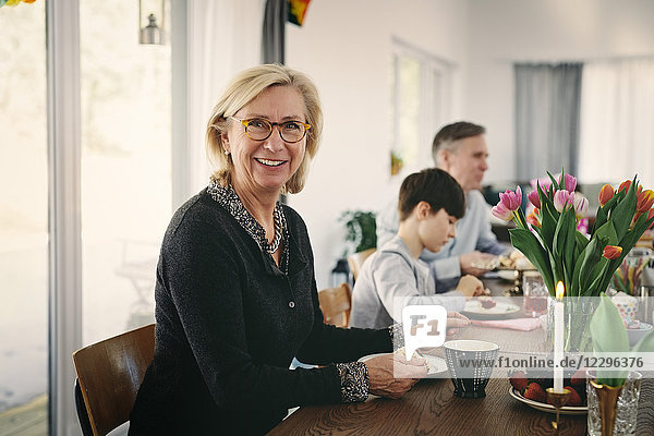 Portrait of smiling grandmother sitting with family at table during party