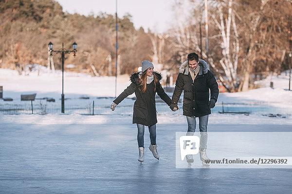 Volle Länge des glücklichen Paares  das sich an den Händen hält  während es auf der Eisbahn Schlittschuh läuft