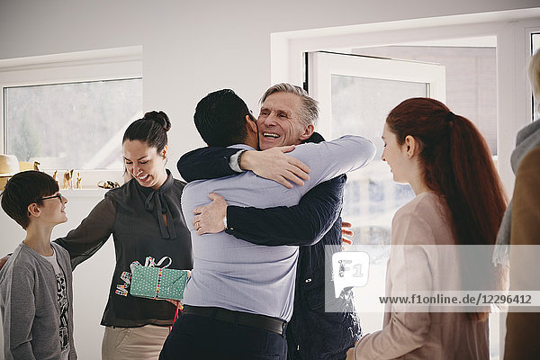 Smiling senior father embracing man while standing by family at doorway