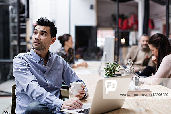 Thoughtful businessman having coffee and using laptop while sitting with colleagues at table