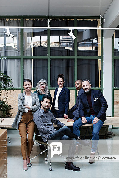 Full length portrait of confident business team at table in creative office