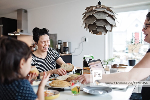 Mother and daughter having food while woman using laptop at dining table