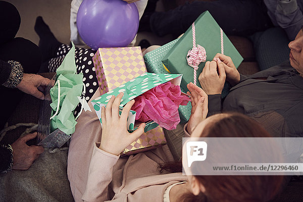 High angle view of girl receiving birthday presents from family at home