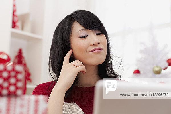 Schöne junge Frau mit Laptop zu Hause